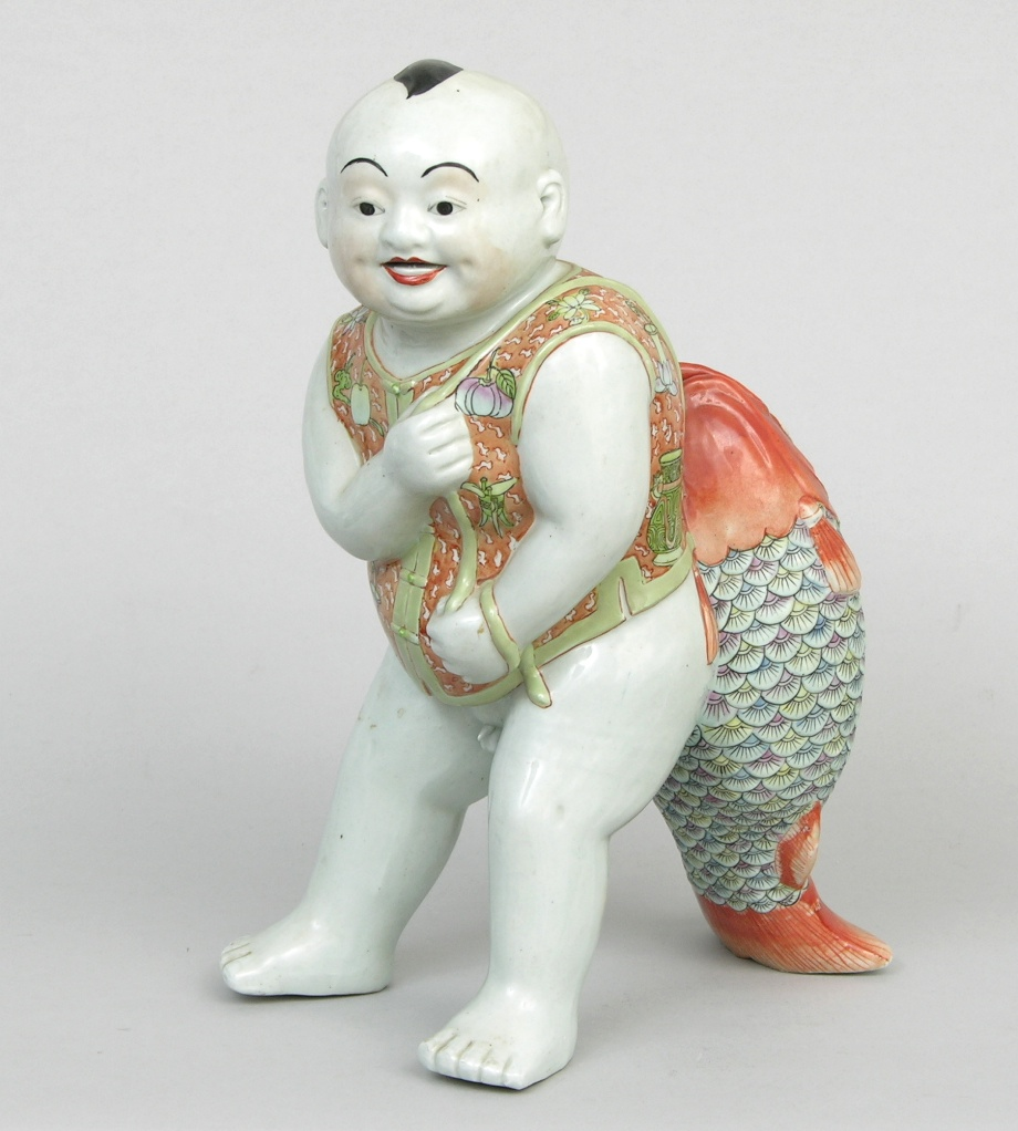 an amusing chinese porcelain figurine of a boy with koi
