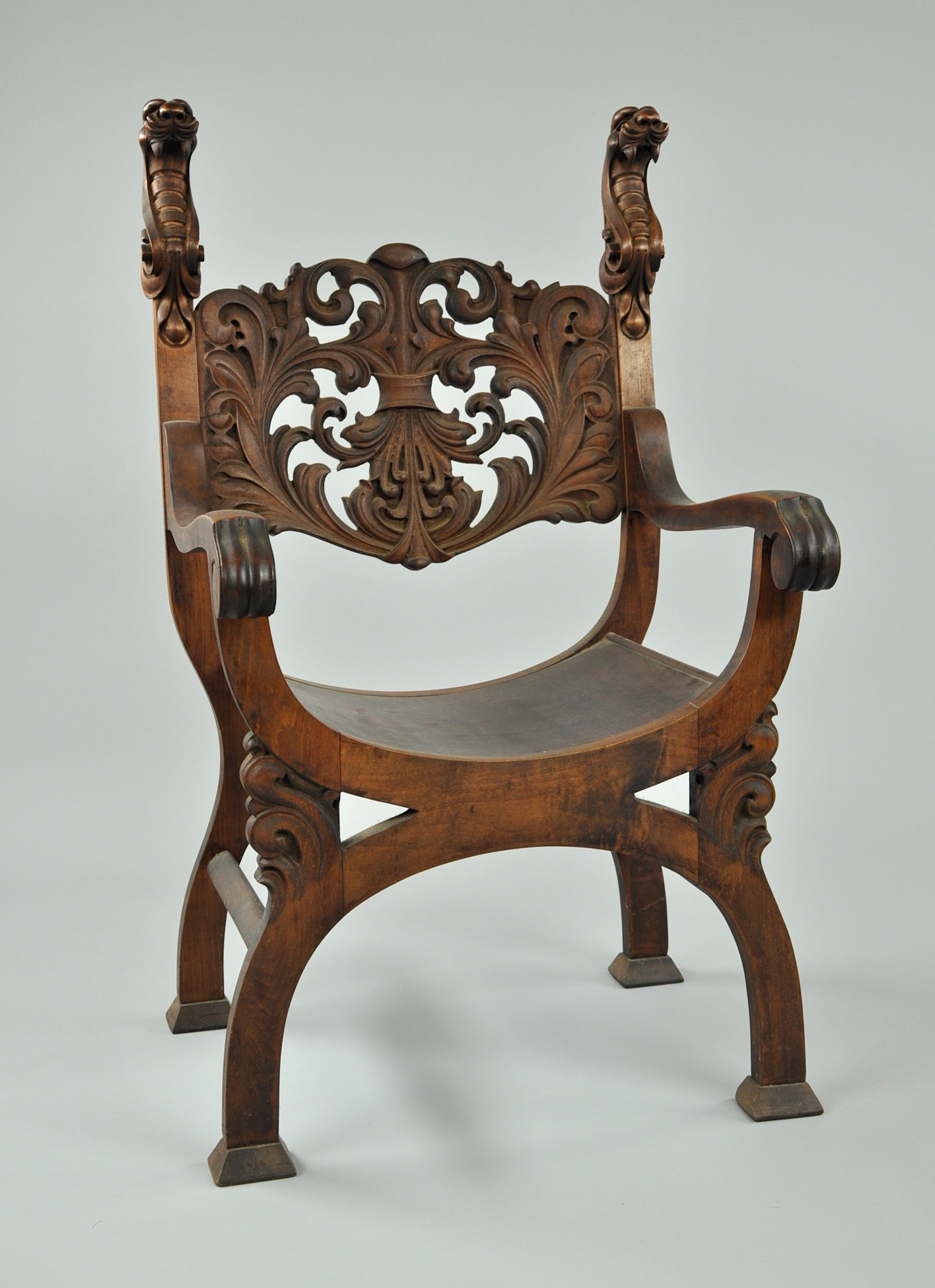 A carved wood arm chair with serpent motif sold